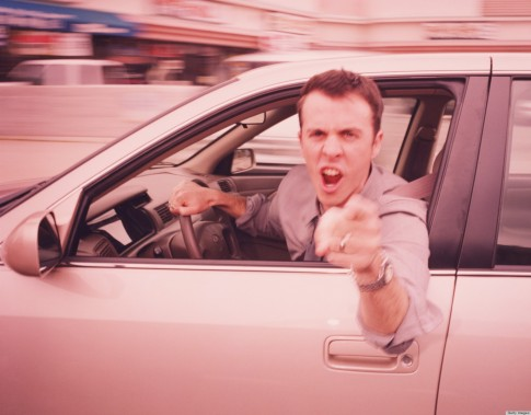 Man driving, leaning out of car, pointing angrily (blurred motion)